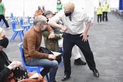 ワクチン接種を待つ人と肘を合わせるジョンソン英首相=ロンドンで5月18日、AP