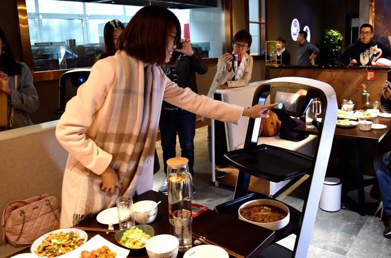 中国のロボットレストランでは、配膳ロボットが料理をテーブルまで運んでくれる=中国・天津市で2018年11月9日、赤間清広撮影