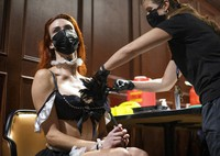 """JoJo Hamner, a cast member of the """"Sexxy After Dark: Where Dinner Meets Play"""" show, gets the Pfizer COVID-19 vaccine during a pop-up vaccine clinic at Larry Flynt's Hustler Club on Friday, May 21, 2021, in Las Vegas. (Ellen Schmidt/Las Vegas Review-Journal via AP)"""