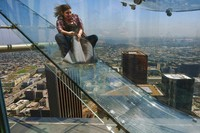 In this June 23, 2016, file photo, a member of the media rides down a glass slide during a media preview at the U.S. Bank Tower building in downtown Los Angeles. (AP Photo/Richard Vogel, File)