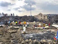 People gather on a stream of cold lava rock following the overnight eruption of Mount Nyiragongo in Goma, Congo, on May 23, 2021. (AP Photo/Clarice Butsapu)