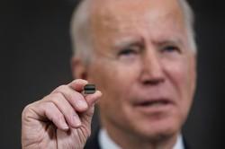 半導体チップを手にするバイデン米大統領。供給網強化の大統領令を出した(今年2月ホワイトハウスで) (Bloomberg)
