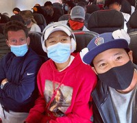Yutaka Nakamura, right, is seen sitting with Naomi Osaka, center, and her coach Wim Fissette on a domestic flight in the U.S. as they head for Europe, in this April 21 photo provided by Nakamura.