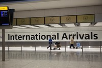 In this Jan. 26, 2021 file photo, arriving passengers walk past a sign in the arrivals area at Heathrow Airport in London, during England's third national lockdown since the coronavirus outbreak began. (AP Photo/Matt Dunham)