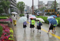 Elementary school students are seen going home in the rain in the city of Kagoshima on May 11, 2021, after it was announced that the rainy season had likely begun in the area. (Mainichi/Junko Adachi)