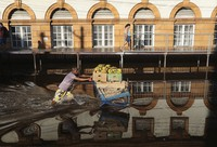A man pushes a shopping cart loaded with bananas through a street flooded by the Negro River in downtown Manaus, Amazonas state, Brazil, on June 1, 2021. (AP Photo/Edmar Barros)