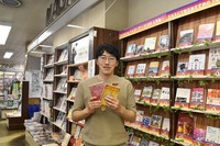 Yasuhiro Konishi is seen holding two of his original cover designs at Seiwado Book Store in Tsurumi Ward, Osaka, on May 15, 2021. (Mainichi/Mai Suganuma)