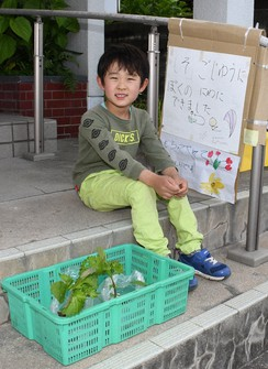"Kosei Maruyama is seen sitting besides a signboard reading, ""Perilla for free. I grew them in the yard,"" in Yukuhashi, Fukuoka Prefecture, on May 25, 2021. (Mainichi/Masaki Matsumoto)"