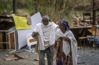 A woman leads a blind man to a visiting doctor, past destroyed furniture and other items in the driveway of a hospital which was damaged and looted by Eritrean soldiers who used it as a base, according to witnesses, in Hawzen, in the Tigray region of northern Ethiopia, on May 7, 2021. (AP Photo/Ben Curtis)