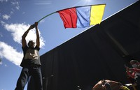 A man waves a banner representing Colombia's national colors during an anti-government protest triggered by proposed tax increases on public services, fuel, wages and pensions, in Bogota, Colombia, on June 2, 2021. (AP Photo/Fernando Vergara)