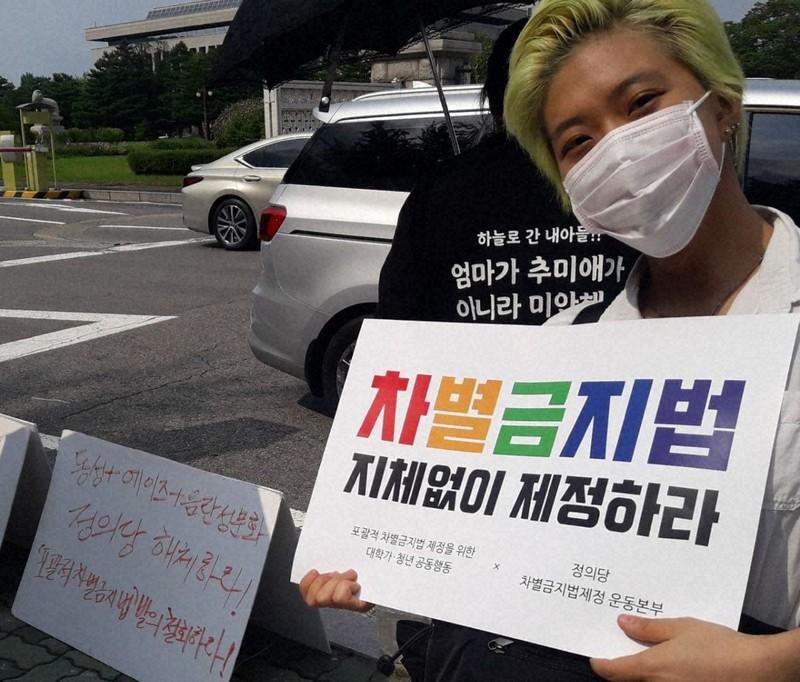 韓国の性的少数者による当事者団体に所属する女性。「差別禁止法 今すぐ制定せよ」と記したプラカードを手にしている=当事者団体「QUV」提供