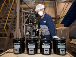 永久磁石の製造に使用されるネオジム鉄粉末の容器を梱包する中国・天津の作業員(Bloomberg)