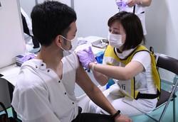 看護師から接種を受ける東京消防庁の職員(左)=2021年6月8日