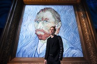 David Korins stands beside a giant replica of celebrated painter Vincent Van Gogh's self portrait at a preview of the Immersive Van Gogh exhibit at Pier 36, on June 4, 2021, in New York. (AP Photo/John Minchillo)