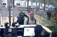This Dec. 30, 2019 image from security camera video shows Michael L. Taylor, center, and George-Antoine Zayek at passport control at Istanbul Airport in Turkey. (DHA via AP, File)