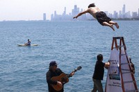 """Dan O'Conor, the """"Great Lake Jumper,"""" makes his 365th leap into Lake Michigan, Saturday, June 12, 2021, in Chicago's Montrose Point. (AP Photo/Shafkat Anowar)"""