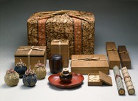 """A tea container named """"Osaka"""" and its accessories are shown in this image provided by Nezu Museum. In the foreground, the tea container is seen placed on a """"tsuishu"""" lacquerware obon tray; to its left are """"shifuku"""" drawstring bags, in which the tea container is wrapped in; behind it is a black """"hikiya"""" canister; and to its right are lids, some of which have cracklike marks called """"su."""" =Important Cultural Property; Tea Container, named Osaka; Seto ware, marutsubo type; Japan Nanbokucho-Muromachi periods, 14th-15th centuries; Nezu Museum"""