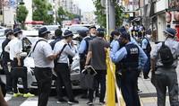 Investigators are seen near a building where a woman was found collapsed, in Osaka's Kita Ward on June 14, 2021. (Mainichi/Tatsuya Fujii)