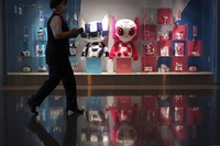 A person walks near the dolls of Miraitowa, left, and Someity, right, official mascots for the Tokyo 2020 Olympics and Paralympics, in Haneda Airport on Monday, June 14, 2021, in Tokyo. (AP Photo/Eugene Hoshiko)