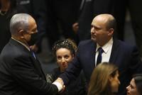Israel's new prime minister Naftali Bennett shakes hands with outgoing prime minister Benjamin Netanyahu during a Knesset session in Jerusalem on June 13, 2021. (AP Photo/Ariel Schalit)