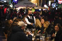 In this Nov. 4, 2020 file photo, a waiter wears a face mask as people eat and drink outside restaurants in Soho, in London. (AP Photo/Alberto Pezzali)