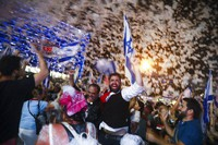 Israelis celebrate the swearing in of the new government in Tel Aviv, Israel, on June 13, 2021. (AP Photo/Oded Balilty)