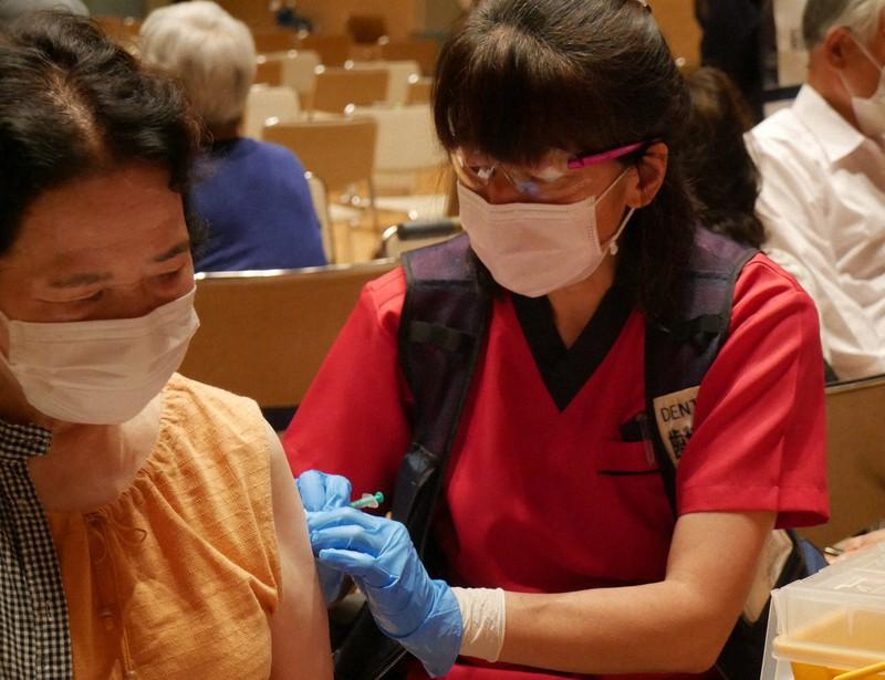 新型コロナウイルスのワクチンを接種する歯科医師(右)=静岡県裾野市民文化センターで2021年6月14日、長沢英次撮影