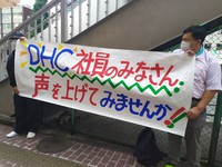In this June 3, 2021 photo, people are seen holding a banner to protest DHC Corp.'s anti-Korean post on its website in front of the company headquarters in Tokyo's Minato Ward. (Mainichi/Harumi Kimoto)