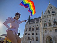 A drag queen waves a rainbow flag during an LGBT rights demonstration in front of the Hungarian Parliament building in Budapest, Hungary on June. 14, 2021. (AP Photo/Bela Szandelszky)