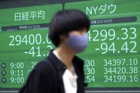 A woman wearing a protective mask walks in front of an electronic stock board showing Japan's Nikkei 225 and New York Dow indexes at a securities firm on June 16, 2021, in Tokyo. (AP Photo/Eugene Hoshiko)