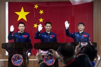 Chinese astronauts, from left, Tang Hongbo, Nie Haisheng, and Liu Boming wave at a press conference at the Jiuquan Satellite Launch Center ahead of the Shenzhou-12 launch from Jiuquan in northwestern China, on June 16, 2021. (AP Photo/Ng Han Guan)