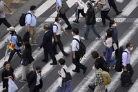 People wearing protective masks to help curb the spread of the coronavirus walk along a pedestrian crossing in Tokyo, on June 16, 2021. (AP Photo/Eugene Hoshiko)
