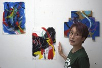 """Japanese artist Miwako Sakauchi speaks about her work for the art exhibition """"Declaration of the end of Olympic games"""" in Chiba near Tokyo, on June 10, 2021. (AP Photo/Eugene Hoshiko)"""