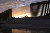 In this June 10, 2021, file photo, a pair of migrant families from Brazil pass through a gap in the border wall to reach the United States after crossing from Mexico to Yuma, Ariz., to seek asylum. (AP Photo/Eugene Garcia)