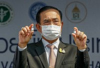 In this Feb. 24, 2021, file photo, Thailand's Prime Minister Prayuth Chan-ocha holds samples of the Sinovac vaccine during a ceremony to mark the arrival of 200,000 doses in a shipment at the Suvarnabhumi airport in Bangkok.  (AP Photo/Sakchai Lalit)