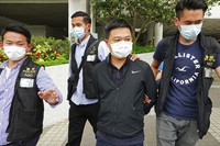 Ryan Law, second from right, Apple Daily's chief editor, is arrested by police officers in Hong Kong on June 17, 2021. (AP Photo)