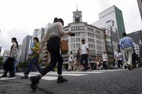 People wearing protective masks to help curb the spread of the coronavirus walk along a pedestrian crossing on June 16, 2021, in Tokyo. (AP Photo/Eugene Hoshiko)