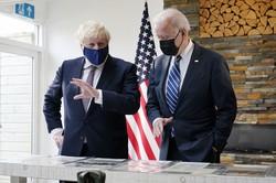 主要7カ国首脳会議(G7サミット)に先立ち行われた米英首脳会談で、大西洋憲章の写しを眺めるジョンソン英首相(左)とバイデン米大統領=英南西部コーンウォールで2021年6月10日、AP