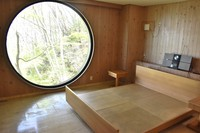 The main bedroom at Capsule House-K, which has a large round window that lets in sunlight, is seen in the town of Miyota, Nagano Prefecture, on May 10, 2021. (Mainichi/Mari Sakane)