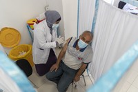 A health care worker administers a dose of the Oxford-AstraZeneca COVID-19 vaccine to a Palestinian man during a vaccination campaign, in the West Bank city of Ramallah, on June 6, 2021. (AP Photo/Nasser Nasser)