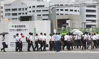Police officers and firefighters arrive to receive the Moderna coronavirus vaccine at a former Tsukiji fish market which was turned to be a temporary mass vaccination center site set up by Tokyo metropolitan government in Tokyo on June 16, 2021. (AP Photo/Koji Sasahara)