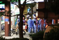Police officers and others are seen gathered in front of a building containing an internet cafe where a man has taken a woman hostage, in Saitama's Omiya Ward on the night of June 17, 2021. (Mainichi/Naotsune Umemura)