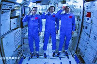 In this photo released by Xinhua News Agency, Chinese astronauts salute after successfully entering the Tianhe space station module as they are displayed on a big screen at the Beijing Aerospace Control Center in Beijing, on June 17, 2021. (Jin Liwang/Xinhua via AP)