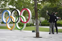 In this June 2, 2021, file photo, men gesture near the Olympic Rings, in Tokyo. Public sentiment in Japan has been generally opposed to holding the Tokyo Olympics and Paralympics. (AP Photo/Eugene Hoshiko)