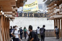 Anti-Olympic protesters hold banners with anti-Olympic slogans outside of the Village Plaza near Tokyo 2020 Olympic and Paralympic Village in Tokyo on Sunday, June 20, 2021. The signs read