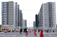 Journalists line up to enter the Village Plaza near Tokyo 2020 Olympic and Paralympic Village during a media tour on Sunday, June 20, 2021, in Tokyo. (AP Photo/Eugene Hoshiko)