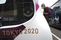 A journalist looks at an autonomous electric vehicles which will be used around the main facilities during a press tour of the Tokyo 2020 Olympic and Paralympic Village on Sunday, June 20, 2021, in Tokyo. (AP Photo/Eugene Hoshiko)