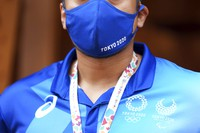 A Tokyo 2020 Olympic and Paralympic staffer wearing a protective mask stands at the entrance to the Village Plaza near Tokyo 2020 Olympic and Paralympic Village on Sunday, June 20, 2021, in Tokyo. (AP Photo/Eugene Hoshiko)