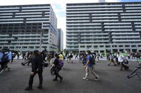 Journalists walk on a road during a press tour of the Tokyo 2020 Olympic and Paralympic Village on Sunday, June 20, 2021, in Tokyo. (AP Photo/Eugene Hoshiko)