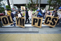 In this May 9, 2021, file photo, people who are against the Tokyo 2020 Olympics set to open in July, march to protest around Tokyo's National Stadium during an anti-Olympics demonstration. (AP Photo/Eugene Hoshiko, File)